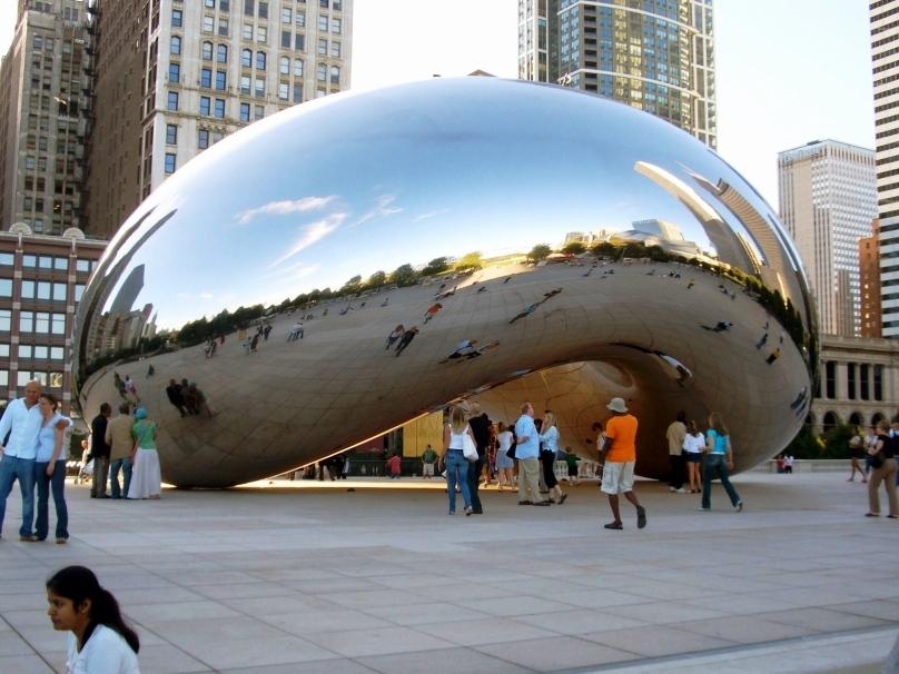"""O Cloud Gate é uma grande estrutura de metal polido idealizada por Anish Kapoor. Por motivos óbvios, a escultura localizada na Praça AT&T do Millenium Park ganhou o apelido de """"the bean"""", o feijão"""