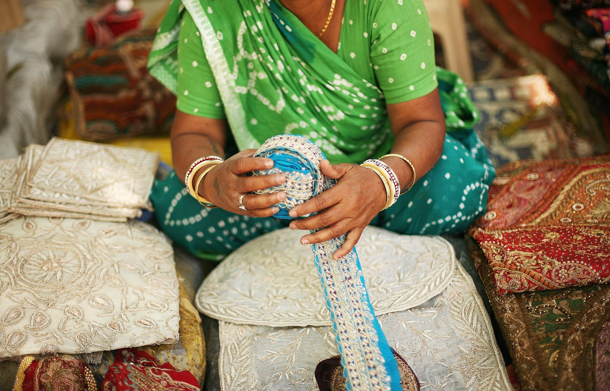 Mulher vende seda em mercado em Délhi, Índia