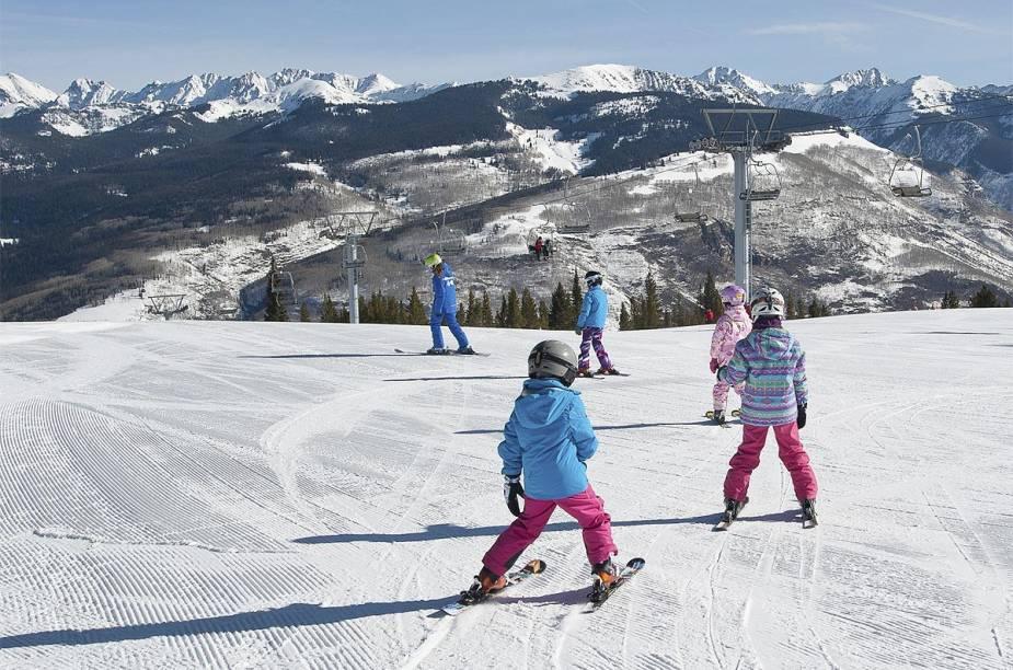 Crianças praticam as primeiras esquiadas na neve