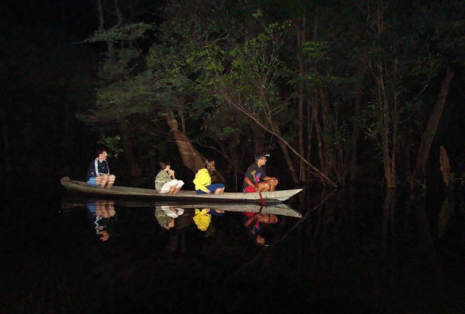 """Durante a focagem noturna do <a href=""""http://viajeaqui.abril.com.br/estabelecimentos/br-am-manaus-hospedagem-amazon-tupana-lodge"""" rel=""""Amazon Tupana Lodge"""" target=""""_blank"""">Amazon Tupana Lodge</a>o guia procura por jacarés. Os olhos dos animais refletem a luz facilitando a observação"""