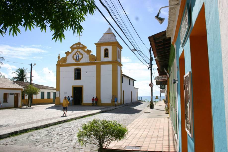 A Igreja de Nossa Senhora d'Ajuda foi erguida no centro de Arraial dAjuda em 1549. O mirante atrás da Igreja oferece uma visão panorâmica que tem o Arraial d'Ajuda Eco Park em primeiro plano e, ao fundo, o mar azul de Porto Seguro na Bahia