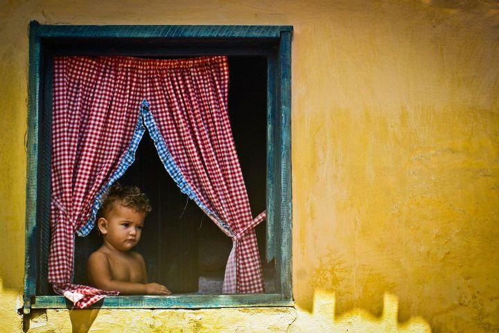 Uma pequena nordestina na janela de sua casa, em Canoa Quebrada, Ceará
