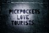 Stêncil na parede com a frase 'Pickpockets love tourists' - batedores de carteiras amam turistas