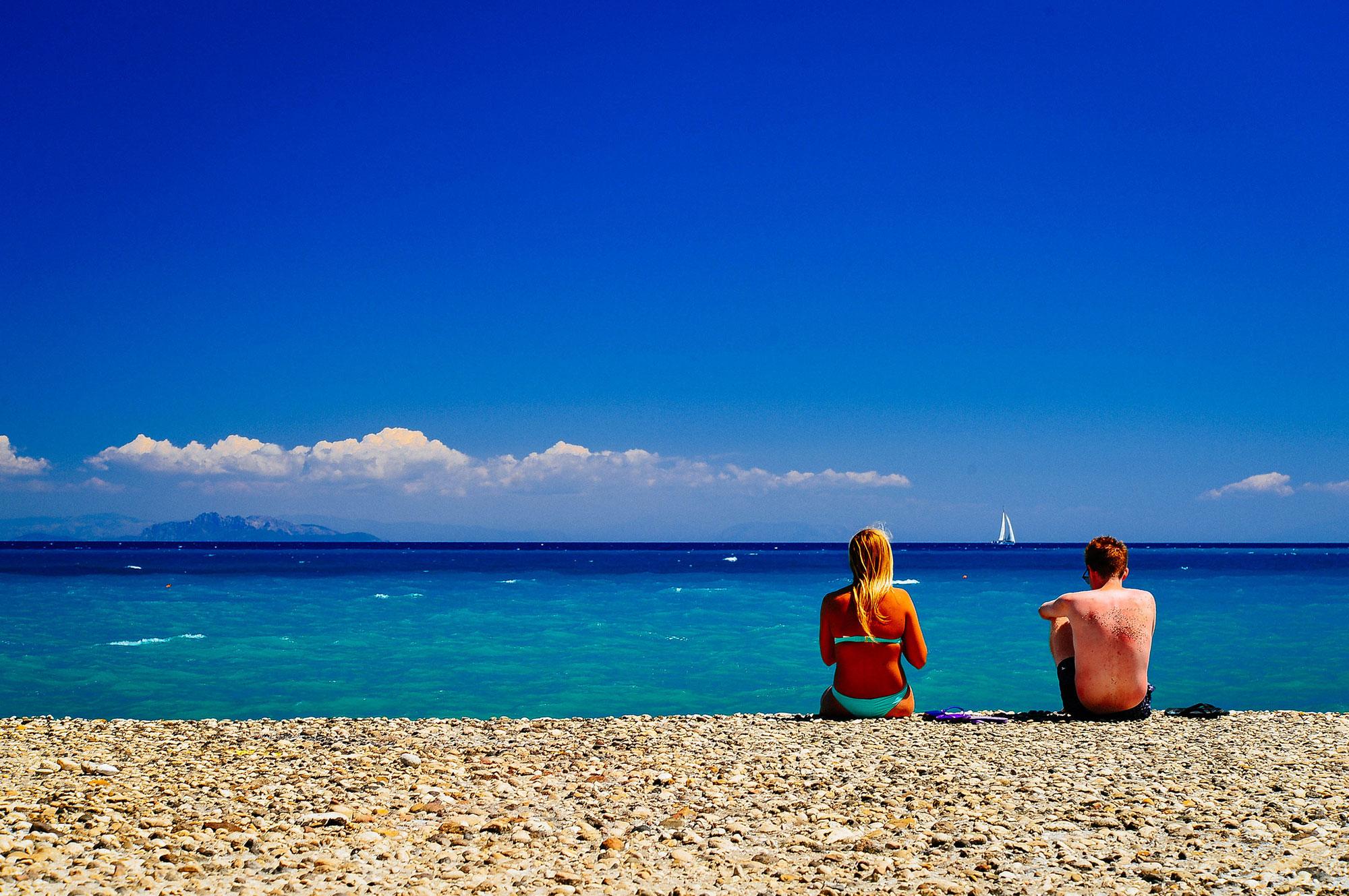 Casal de turistas em praia da Grécia