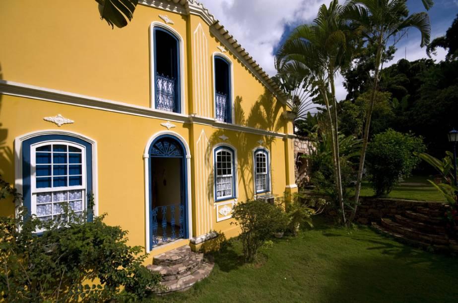 Fachada e jardim lateral da Alcino Estalagem & Atelier, em Lençóis, casarão de 1890 restaurado e transformado em pousada