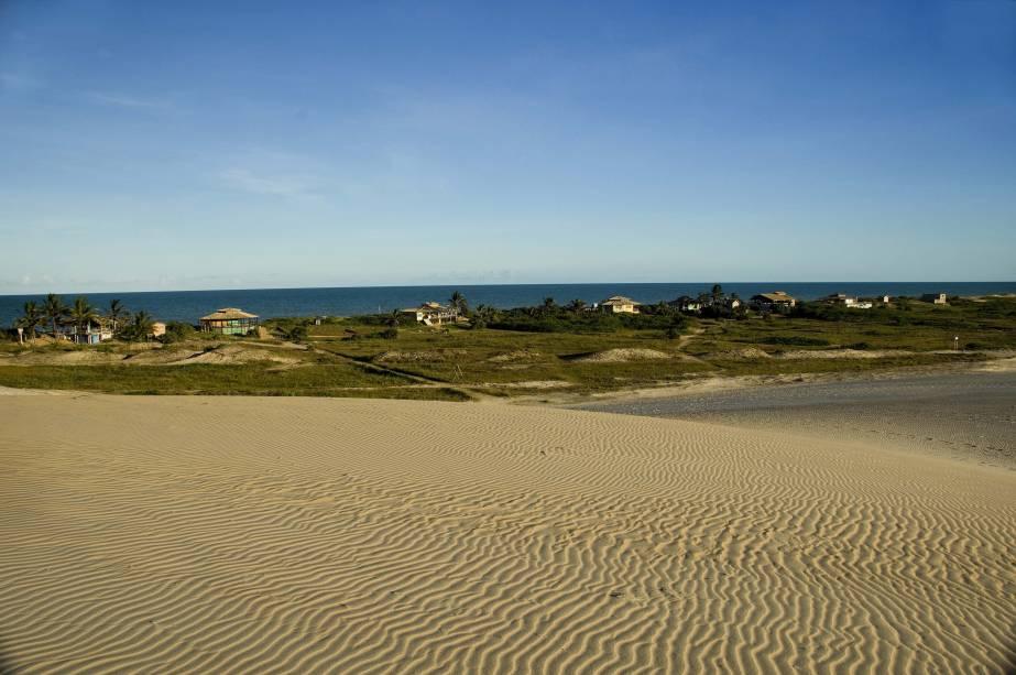 A praia de Itaúnas, em Conceição da Barra (ES), é cercada pelas dunas que soterraram a antiga vila nos anos 60. Conta com bares que servem petiscos e dispõem cadeiras e guarda-sol para os clientes.