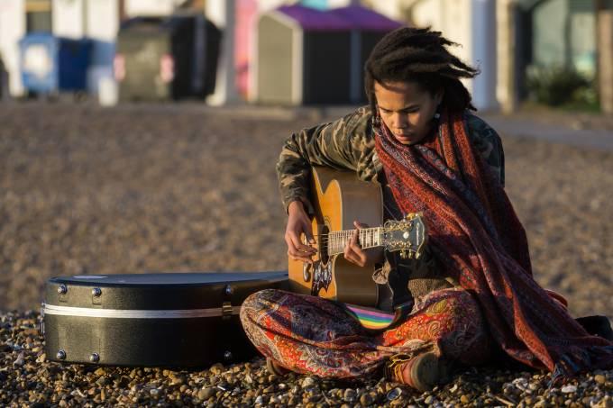 Garota toca violão em praia de Brighton, Inglaterra Flickr