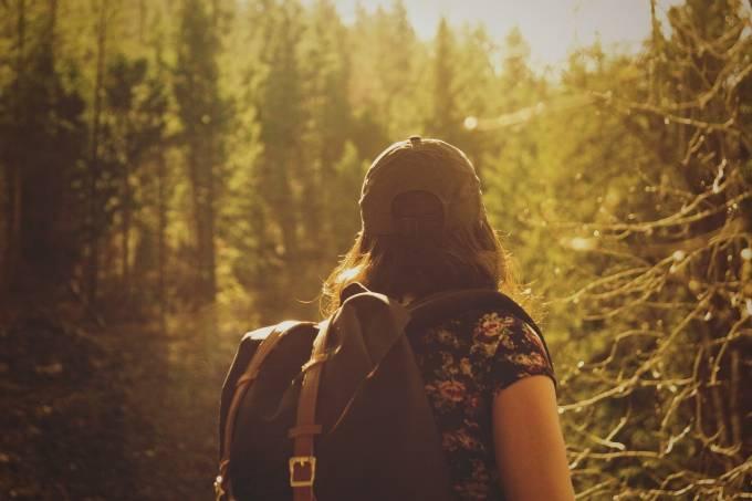 Mulher de costas e boné com mochila caminhando em uma floresta de coníferas com o sol lateral