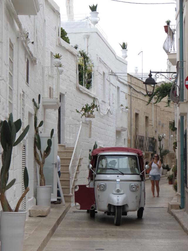 O carrinho Ape e as casinhas brancas: dois ícones da Puglia na mesma foto, em Monopoli