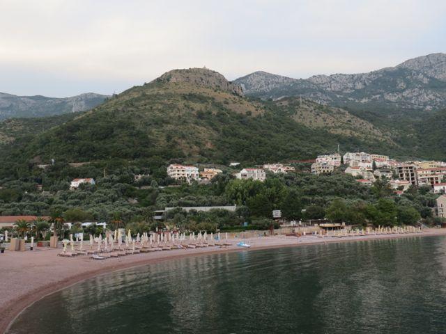 A praia pública de Sveti Stefan no fim de tarde e, ao fundo, o simpático vilarejo onde os mortais se alojam