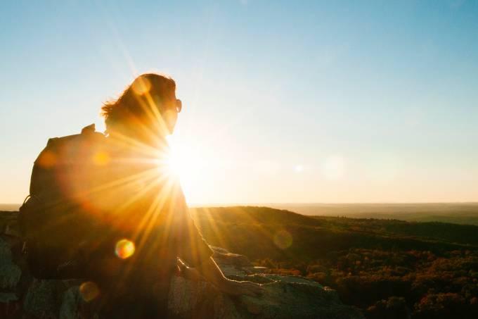 Mulher viajante observa paisagem ao pôr do sol