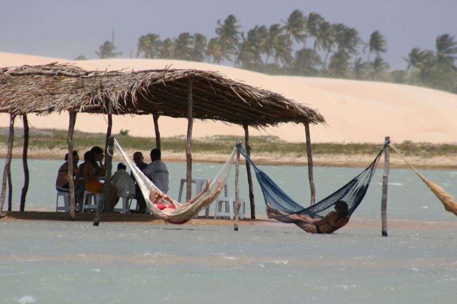 Turistas se refrescam no quiosque e nas redes dentro do mar na praia de Tatajuba, em Camocim, perto de Jericoacoara (CE)