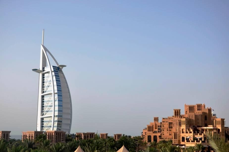 A modernidade das linhas do Burj al-Arab contrastando com a arquitetura tradicional do complexo de lojas e restaurantes de Madinat Jumeirah. Os edifícios têm aproximadamente a mesma idade
