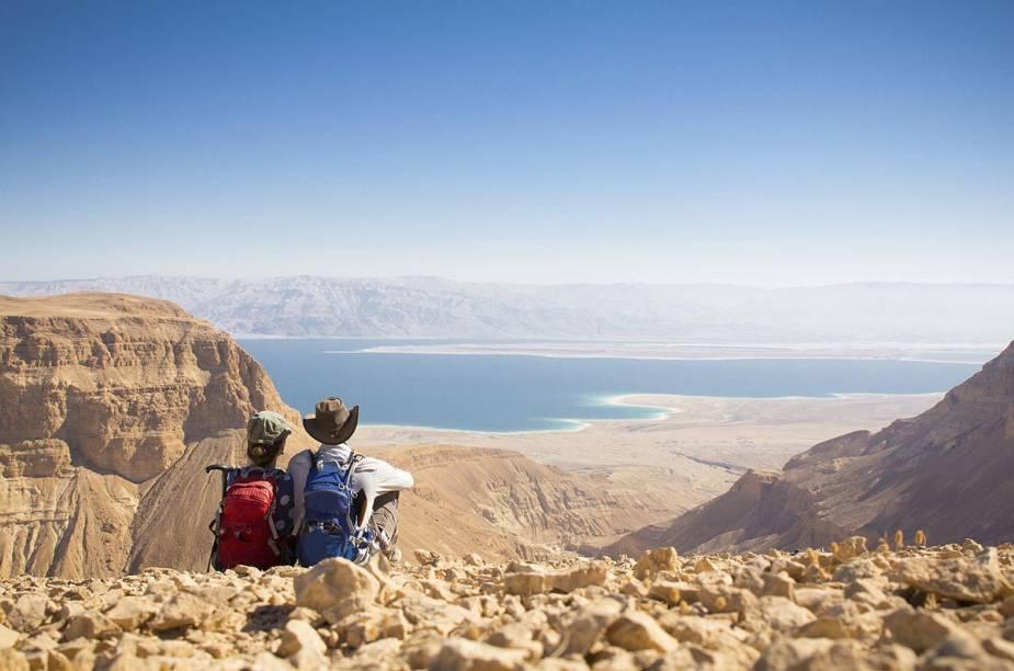 Casal de viajantes observa o Mar Morto do alto de uma colina