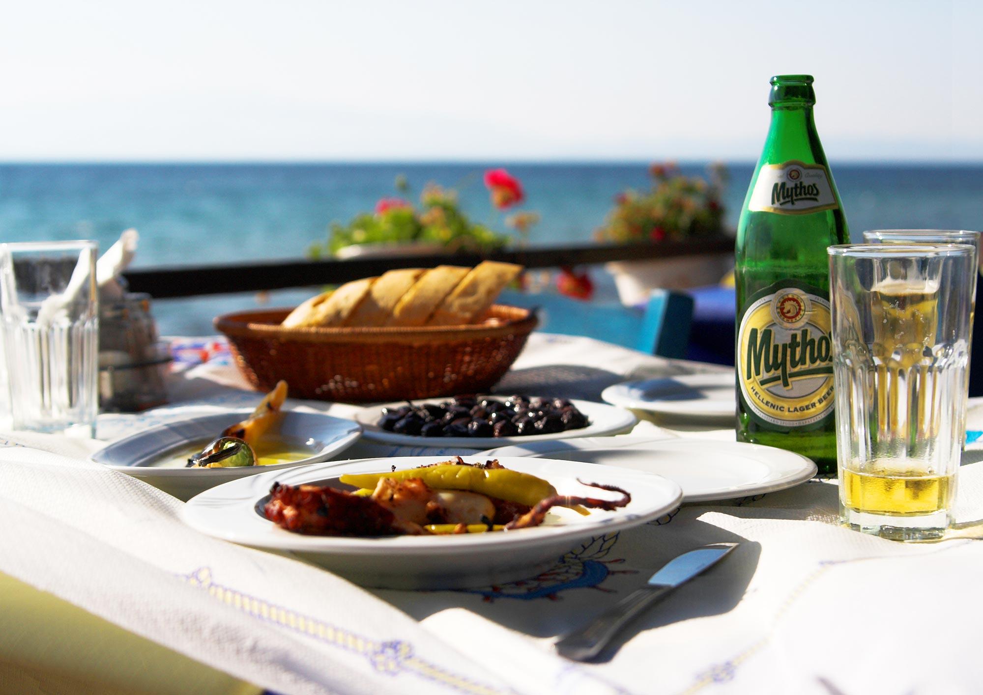 Mesa com polvo grelhado, fava, cerveja Mythos e comidas gregas