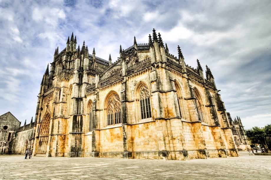"""A movimentação de Batalha gira em torno do impressionante Mosteiro de Santa Maria da Vitória, Patrimônio Histórico pela Unesco, também conhecido como Mosteiro da Batalha (foto). Não é preciso ser especialista em arquitetura para notar a influência gótica que está em cada detalhezinho dessa construção do século 14.<a href=""""https://www.booking.com/searchresults.pt-br.html?aid=332455&sid=605c56653290b80351df808102ac423d&sb=1&src=searchresults&src_elem=sb&error_url=https%3A%2F%2Fwww.booking.com%2Fsearchresults.pt-br.html%3Faid%3D332455%3Bsid%3D605c56653290b80351df808102ac423d%3Bcity%3D-2170637%3Bclass_interval%3D1%3Bdest_id%3D-2157508%3Bdest_type%3Dcity%3Bdtdisc%3D0%3Bfrom_sf%3D1%3Bgroup_adults%3D2%3Bgroup_children%3D0%3Binac%3D0%3Bindex_postcard%3D0%3Blabel_click%3Dundef%3Bno_rooms%3D1%3Boffset%3D0%3Bpostcard%3D0%3Braw_dest_type%3Dcity%3Broom1%3DA%252CA%3Bsb_price_type%3Dtotal%3Bsearch_selected%3D1%3Bsrc%3Dsearchresults%3Bsrc_elem%3Dsb%3Bss%3DAlcoba%25C3%25A7a%252C%2520Regi%25C3%25A3o%2520do%2520Centro%252C%2520Portugal%3Bss_all%3D0%3Bss_raw%3DAlcoba%25C3%25A7a%3Bssb%3Dempty%3Bsshis%3D0%3Bssne_untouched%3DNazar%25C3%25A9%26%3B&ss=Batalha%2C+Regi%C3%A3o+do+Centro%2C+Portugal&ssne=Alcoba%C3%A7a&ssne_untouched=Alcoba%C3%A7a&city=-2157508&checkin_monthday=&checkin_month=&checkin_year=&checkout_monthday=&checkout_month=&checkout_year=&group_adults=2&group_children=0&no_rooms=1&from_sf=1&ss_raw=Batalha&ac_position=0&ac_langcode=xb&dest_id=-2159606&dest_type=city&place_id_lat=39.65806&place_id_lon=-8.82465&search_pageview_id=804d7c599752036d&search_selected=true&search_pageview_id=804d7c599752036d&ac_suggestion_list_length=5&ac_suggestion_theme_list_length=0"""" target=""""_blank"""" rel=""""noopener""""><em>Busque hospedagens em Batalha</em></a>"""