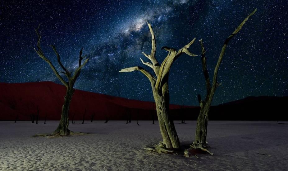 """<strong>8. <a href=""""http://viajeaqui.abril.com.br/vt/blogs/achados/category/africa/namibia/"""" target=""""_blank"""" rel=""""noopener"""">Deserto da Namíbia</a></strong>Com suas árvores secas e dunas vermelhas, a Reserva Natural da Namíbia poderia ser um local intergaláctico em si. O deserto remoto é um dos lugares mais """"escuros"""" do mundo. Como uma reserva internacional Dark Sky, o local tem investido em sua preservação utilizando apenas lâmpadas vermelhas econômicas que não causam impacto sobre os níveis de poluição luminosa<a href=""""http://viajeaqui.abril.com.br/vt/blogs/achados/2016/03/21/10-motivos-para-conhecer-a-namibia/"""" target=""""_blank"""" rel=""""noopener"""">+ 10 motivos para você conhecer a Namíbia</a>"""