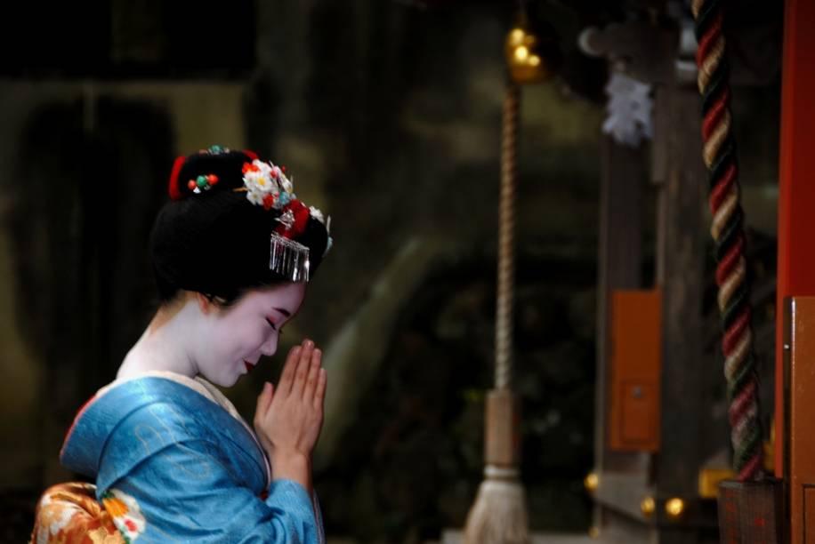 Aprendiz de geisha, conhecidas como maiko, faz oração no santuário xintoísta Matsuo Taisha, em Kyoto