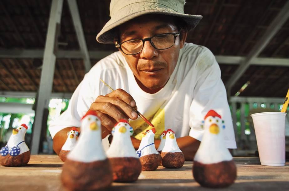 O artista plástico Carcará em seu ateliê. Símbolos do lugar, galinhas de todos os tipos enchem as vitrines do povoado