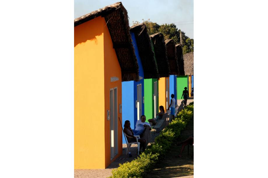 Moradores diante do casario colorido típico da cidade de São Pedro do Piauí (PI)