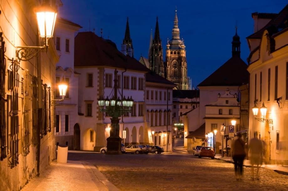 A cidade de Praga convida as pessoas a andar de mãos dadas, admirando a encantadora luz sobre o histórico casario