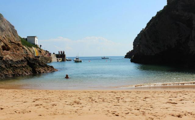 O mar parece mais uma piscina de tão calmo; dá para ver peixes nadando até perto da praia