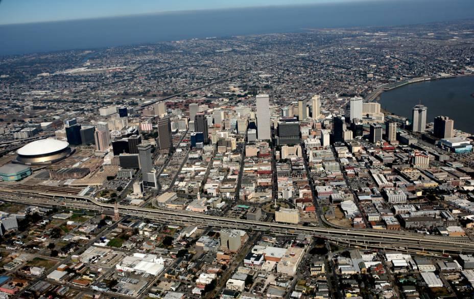 Vista aérea de Nova Orleans, com o estádio Super Dome à esquerda. À direita, uma ponta do rio Mississippi e, no fundo, o lago Ponchartrain