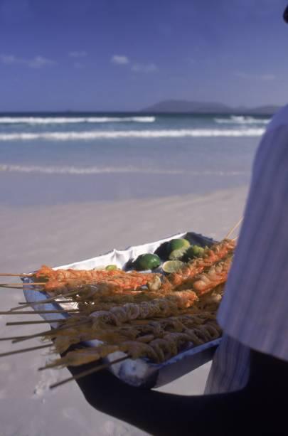 Garoto vendendo espeto de camarão numa praia de Cabo Frio (RJ)
