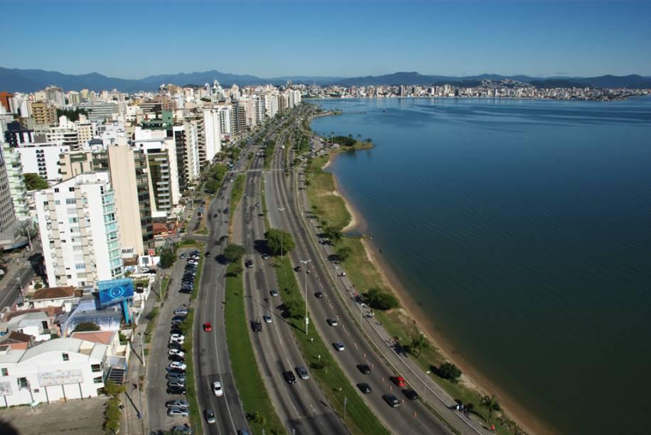 """Em <a href=""""http://viajeaqui.abril.com.br/cidades/br-sc-florianopolis"""" rel=""""Florianópolis (SC)"""" target=""""_blank"""">Florianópolis (SC)</a>, o turista pode optar pelas areias badaladas e urbanizadas na orla norte ou se entregar às sossegadas e selvagens praias do sul; umas com ondas violentas, outras de águas calmas, longos trechos de areia e pequenos paraísos escondidos"""