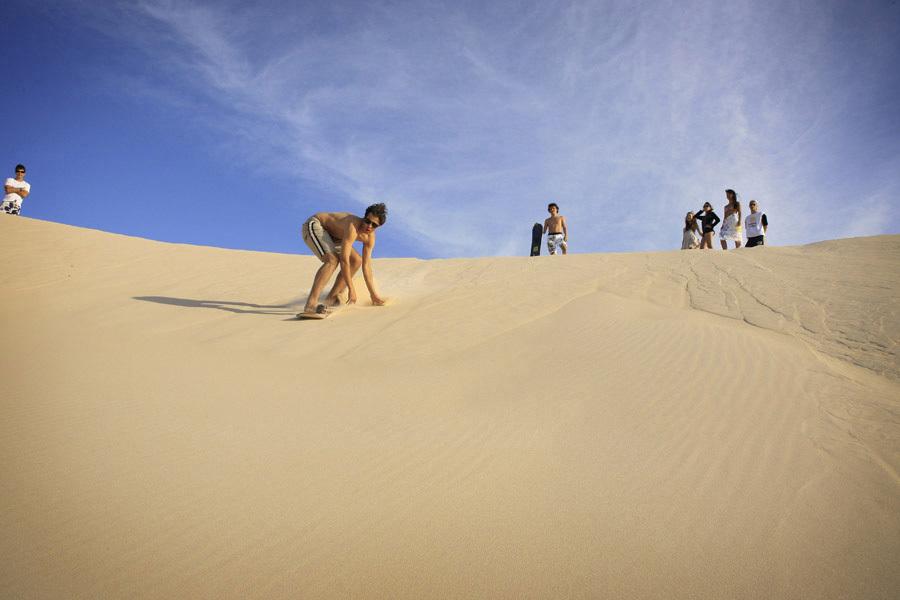 Extensa, com areia branca e firme, dunas ao fundo e mar de ondas fortes, a Praia do Santinho, em Floripa (SC) é um ótimo lugar para caminhadas e para a prática de sandboard