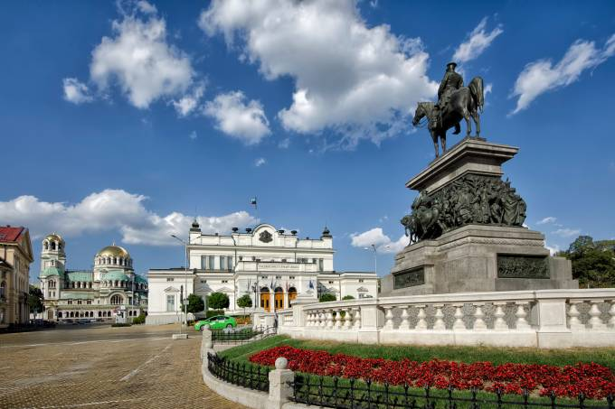 A Praça do Parlamento, com o Prédio do Parlamento e a Catedral de St. Alexander Nevsky ao fundo, em Sofia, Bulgária