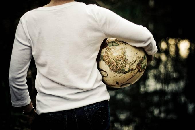 Mulher viajante de costas segurando um globo retrô embaixo do braço