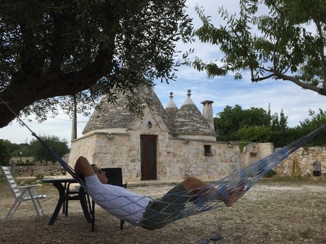O bem bom à sombra das oliveiras e nosso trullo ao fundo