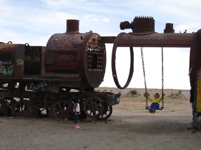 Crianças brincando no cemitério de trens em Uyuni, Bolívia