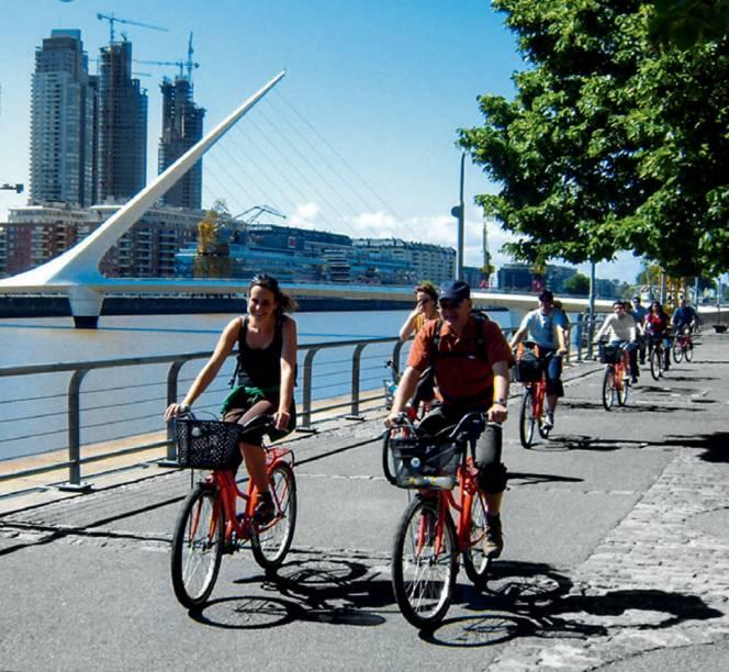 """Ciclistas passeiam pelo calçadão cheio de bares, cafés e restaurantes em Puerto Madero, <a href=""""http://viajeaqui.abril.com.br/cidades/ar-buenos-aires/"""" rel=""""Buenos Aires"""">Buenos Aires</a>"""