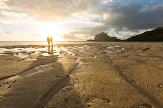 Vilfredo e Heloisa Schurmann apreciam o pôr do sol e a montanha Le Morne ao fundo