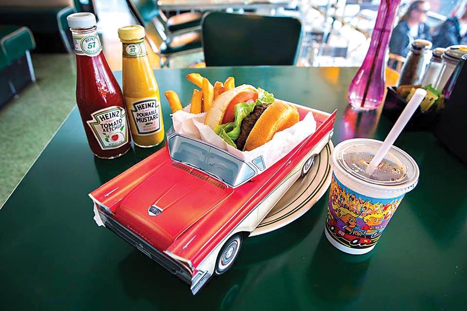 Um hambúrguer e batatas fritas se encontram dentro de um minicarro conversível, que funciona como um prato em cima de uma mesa. Do lado direito, um copo de plástico guarda um refrigerante e, à esquerda, há dois potes: um de ketchup e outro de mostarda