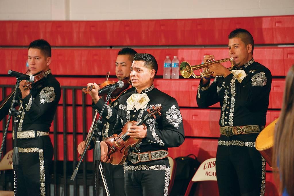 Quatro músicos, três segurando violinos e o quarto um trompete, tocam e cantam para uma plateia, vestidos com fardas típicas pretas com detalhes em branco