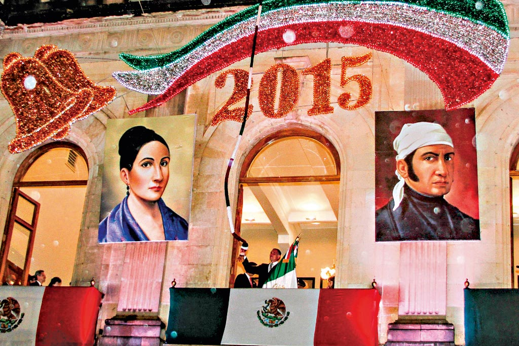 Em uma varanda de um edifício decorado com bandeiras e símbolos com as cores do México, um homem de autoridade no centro, segurando uma bandeira