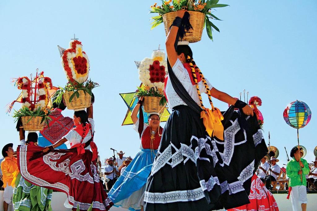 Mulheres dançam ao som de um grupo musical ao vivo, com longas tranças e saias compridas. Em uma mão, seguram uma cesta de flores apoiada na cabeça, enquanto com a outra levantam uma ponta da saia para dançar