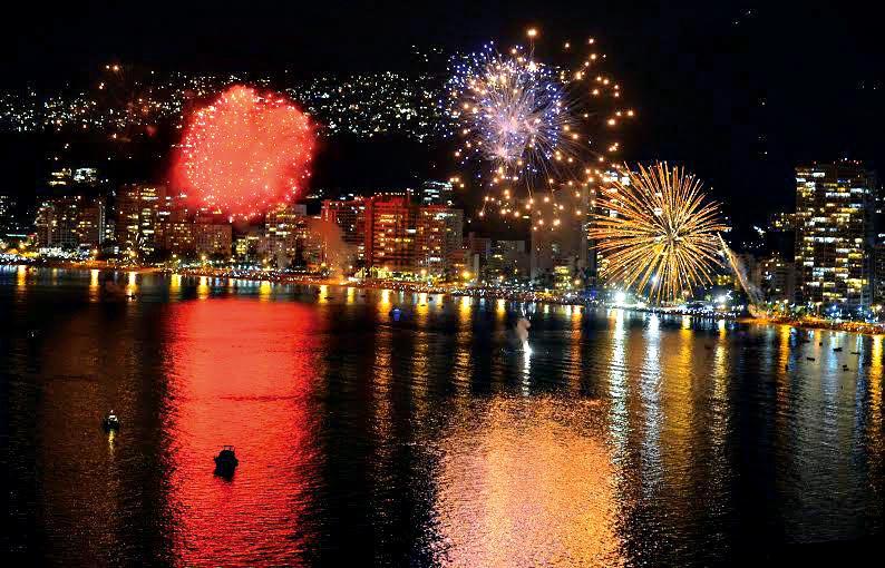 A cena mostra a cidade de Acapulco em frente ao mar, com fogos de artifício em abundância estourando por cima da praia