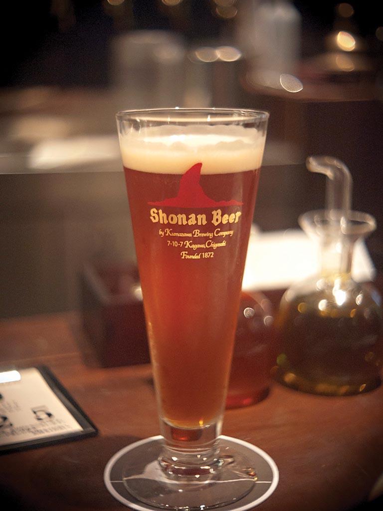 Uma taça alta de cerveja japonesa, com fundo de um bar