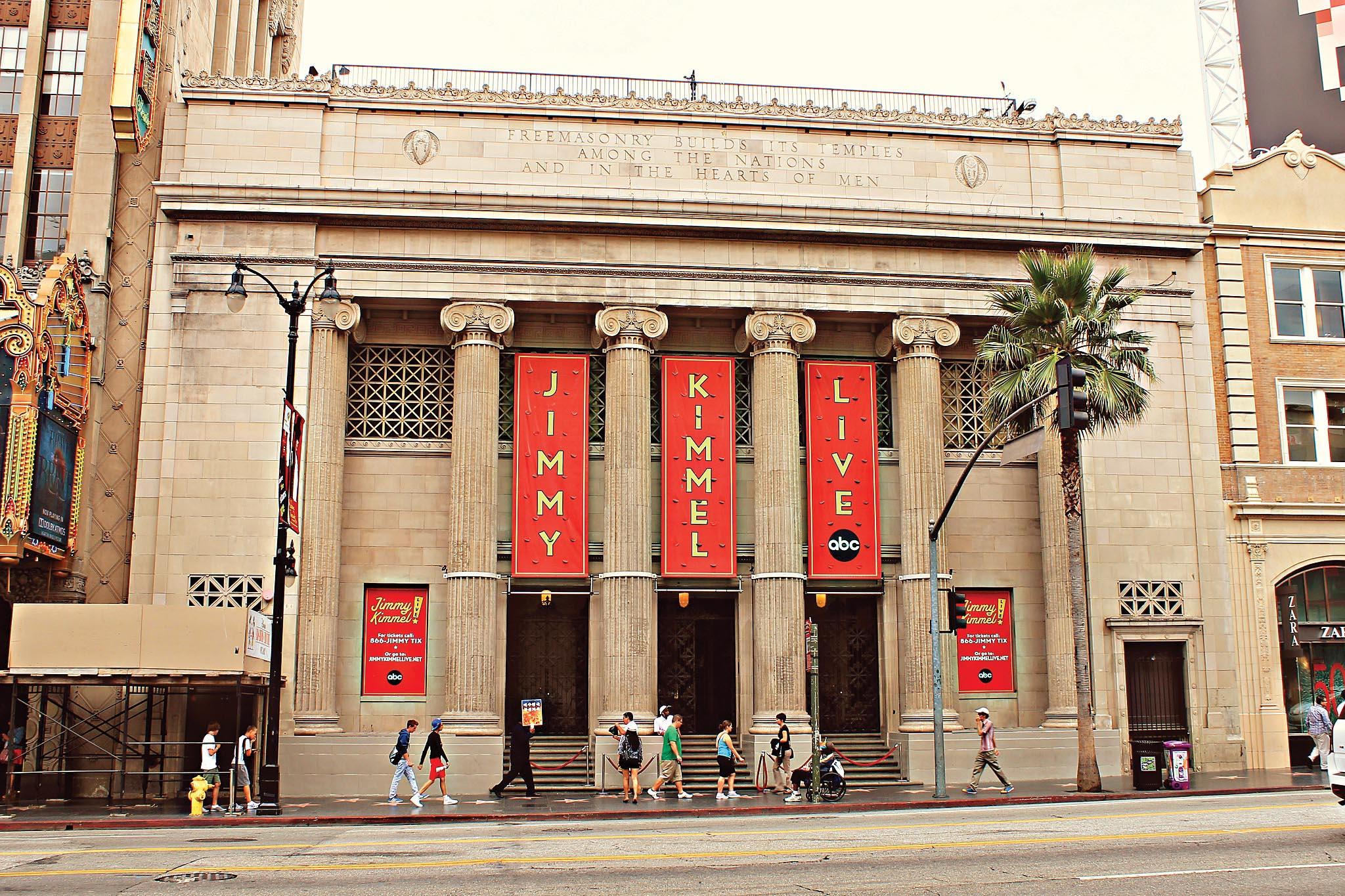 """Um prédio com arquitetura e colunas que fazem referência à cultura grega. Entre as colunas, há três faixas verticais. Em cada uma delas encontram-se as palavras """"jimmy"""", """"kimmel"""" e """"live"""". Algumas pessoas caminham tranquilamente pela frente do prédio"""