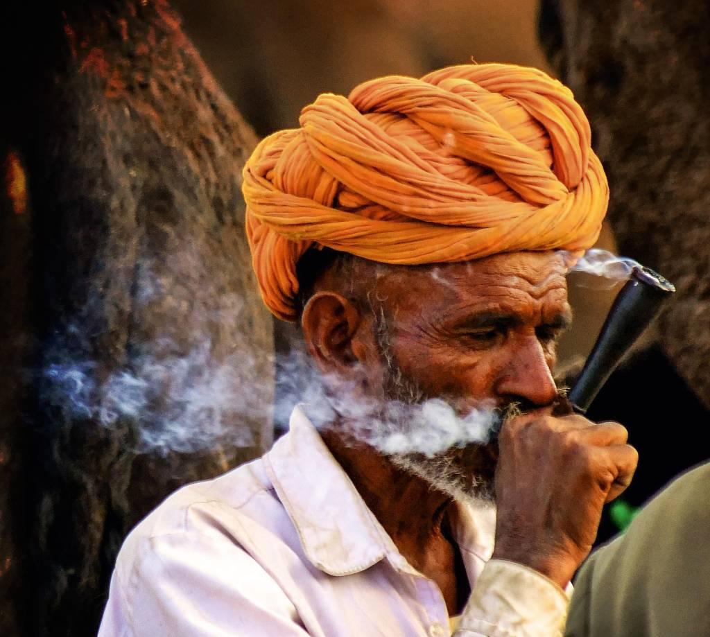 Homem de turbante fuma chilam, soltando uma trilha de fumaça de sua boca