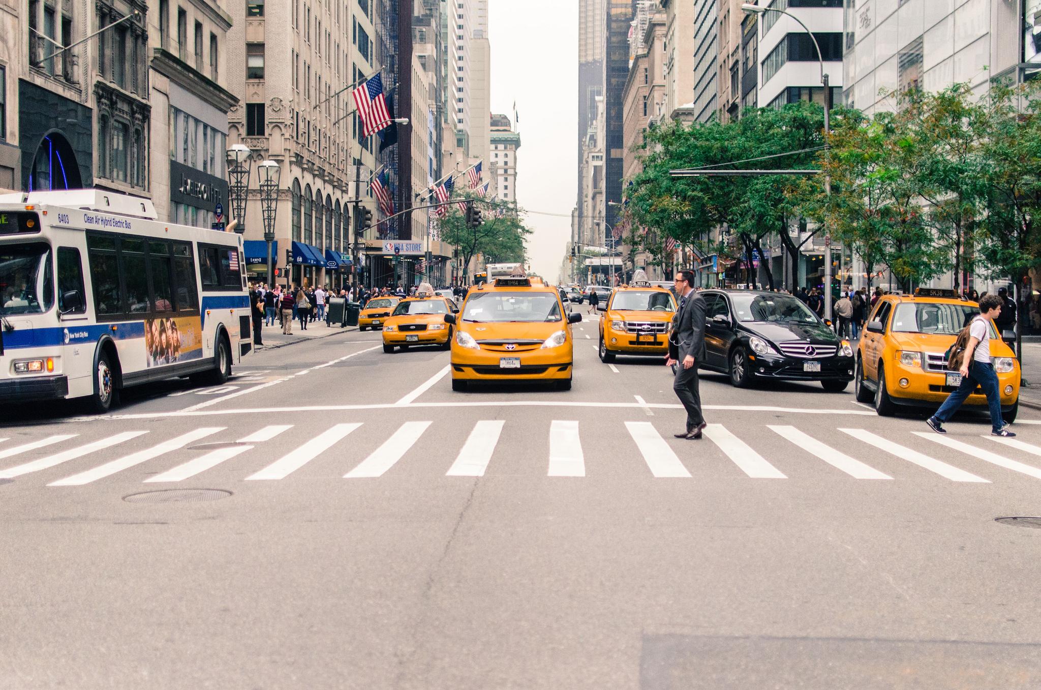 Homem atravessa a rua na faixa de pedestres em avenida de Nova York