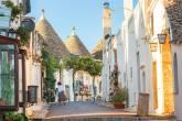 """Uma ruazinha com várias casas no estilo arquitetônico trulli, em """"cone"""""""