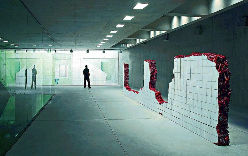 Uma parede incompleta fica no meio do comôdo, destruída na parte de cima e modificada na parte interna de modo a parecer que é feita de vísceras