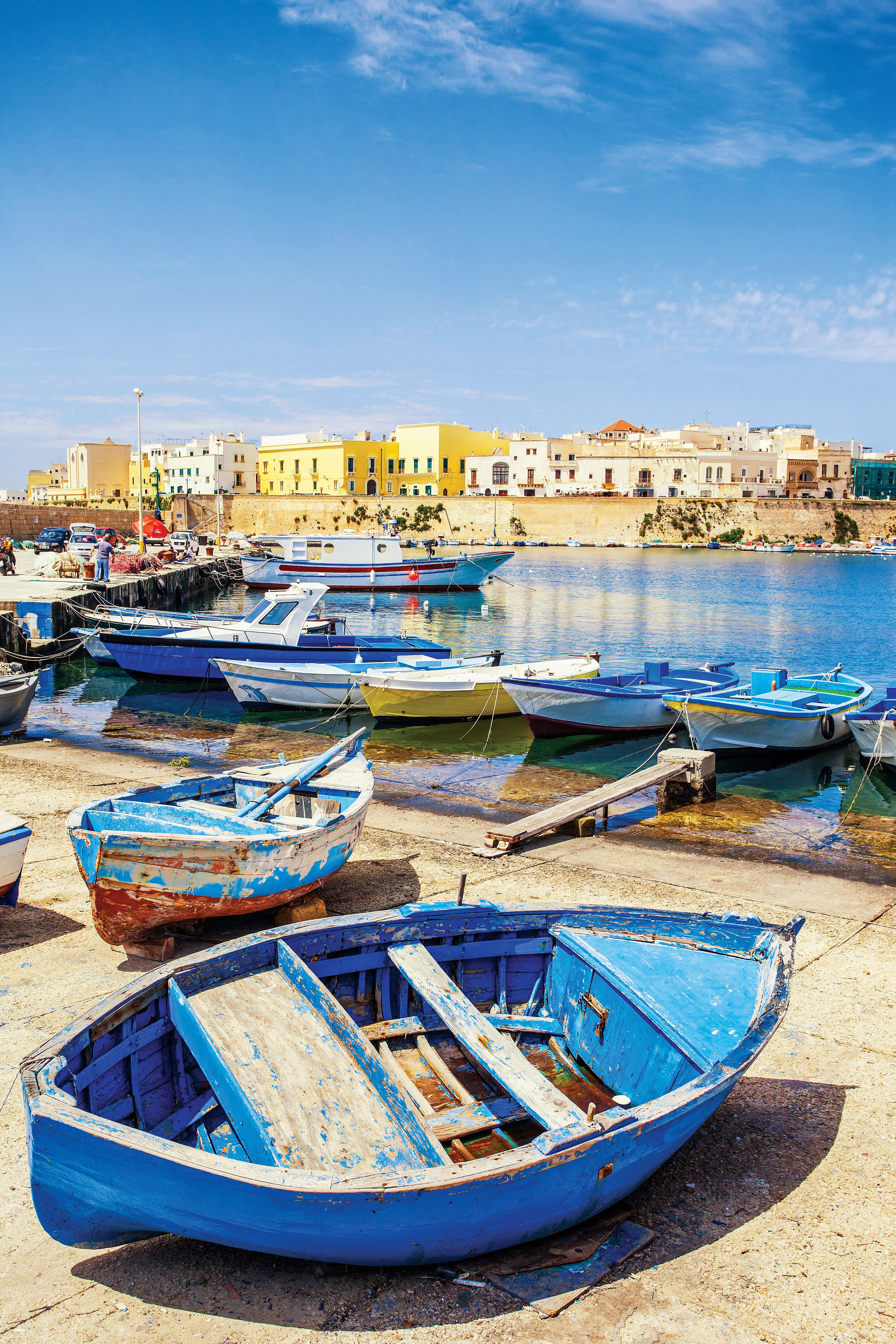 Pequenos barquinhos ancorados em um pequeno porto. Ao fundo, a fortaleza à beira-mar