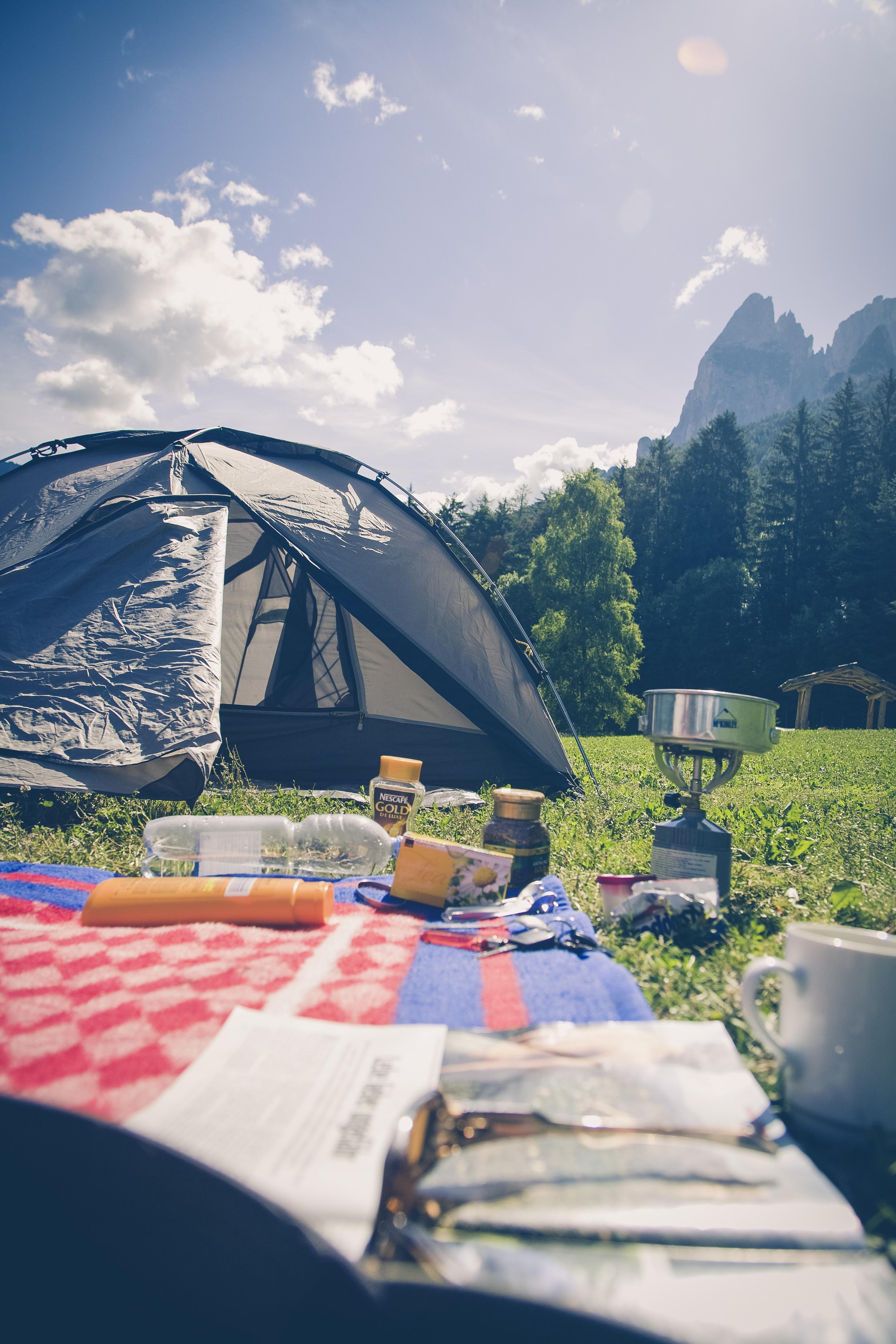 Gramado com barraca de camping, fogareiro e canga em um dia de sol num campo aberto