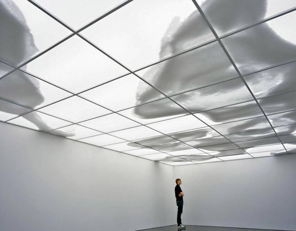 Uma pessoa, sozinha, se encontra em um quarto desprovido de móveis, com um teto onde sombras se movem, tomando a forma de nuvens